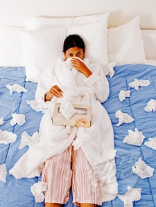 Sick Indian woman blowing nose in bed